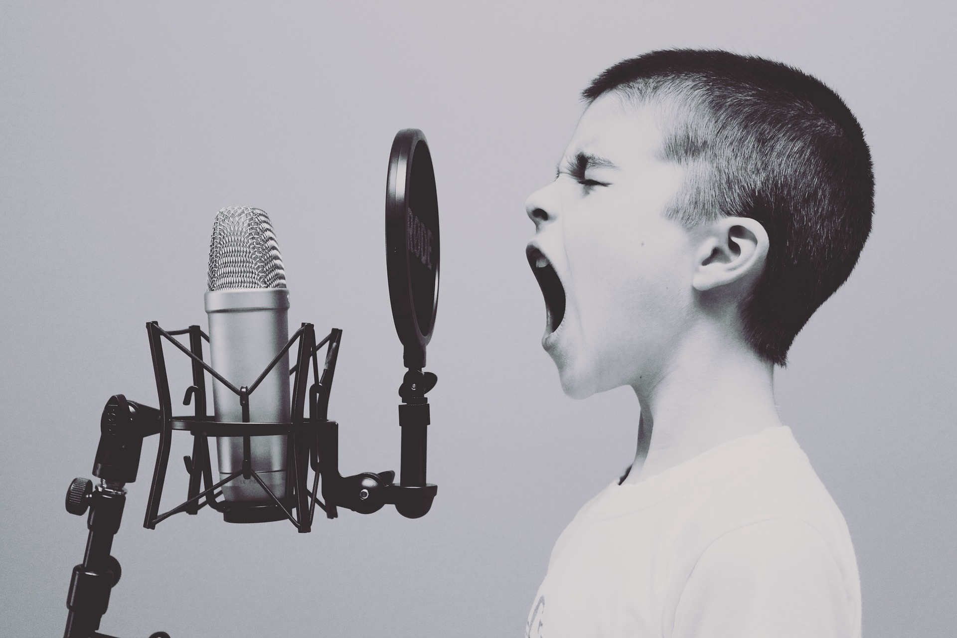 Image is black and white with a boy's profle screaming into a microphone