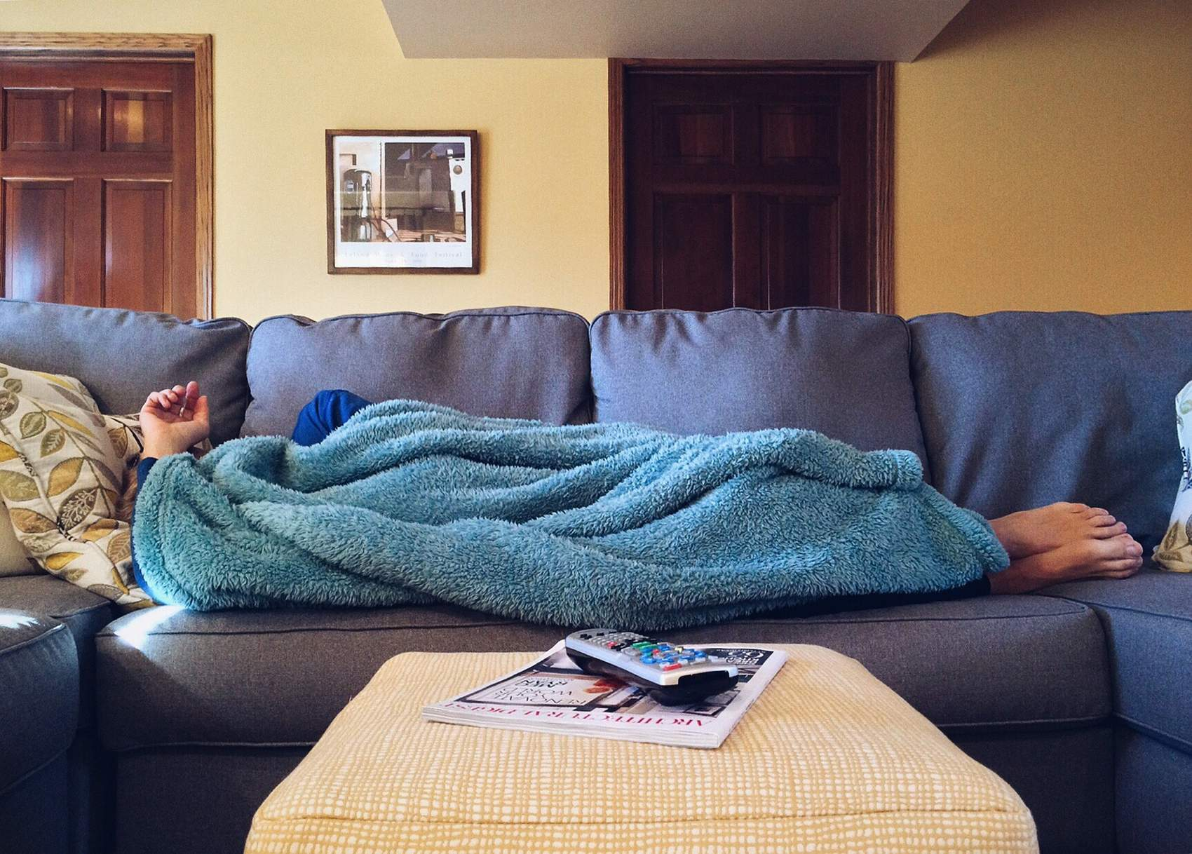 A woman is sleeping on a gray coush with a blue blanket covering her body and her head, only her feet and one hand are showing.