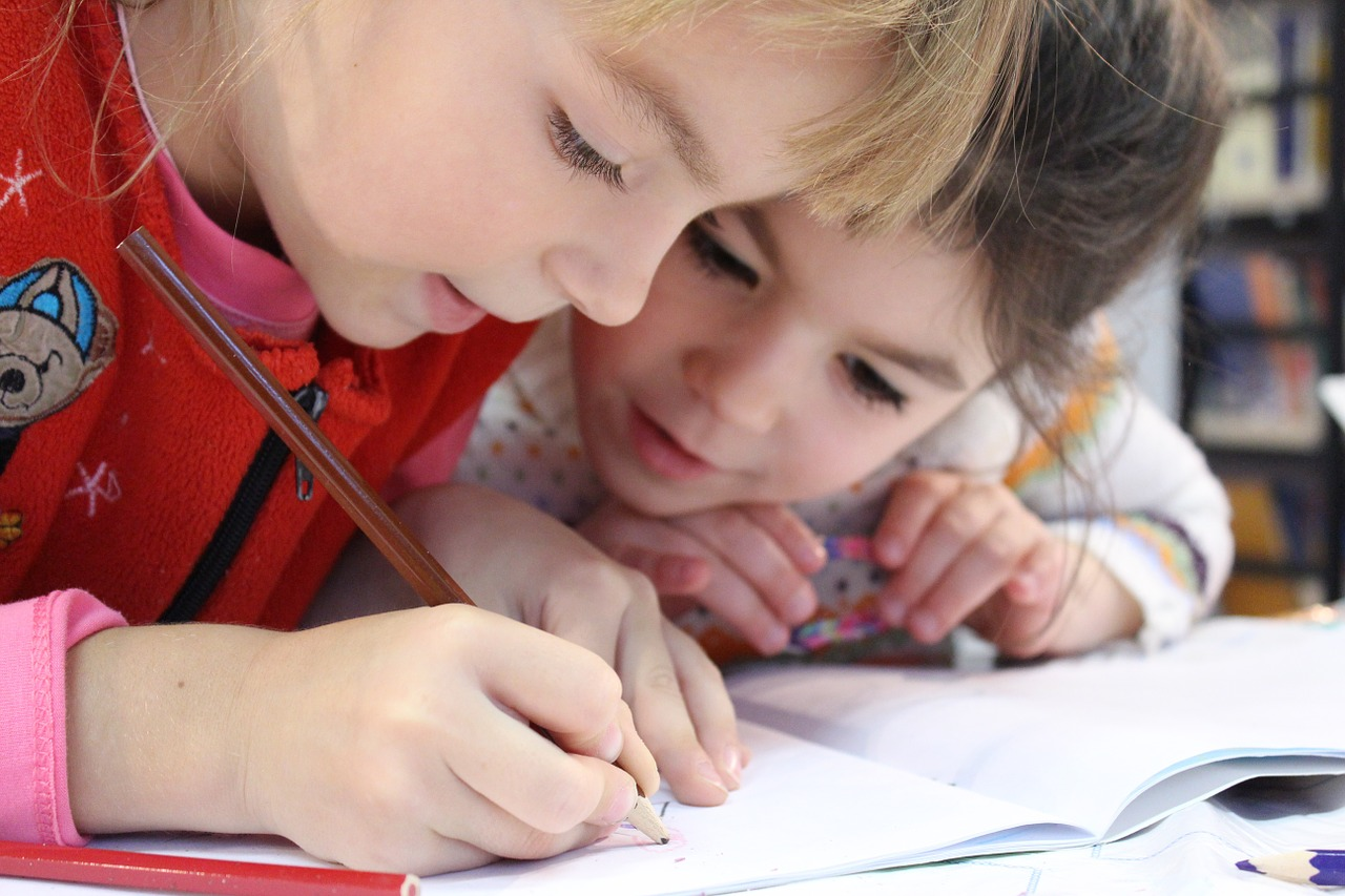 Image is a close up of two little girls, one is writing on a notebook, the other is watching her