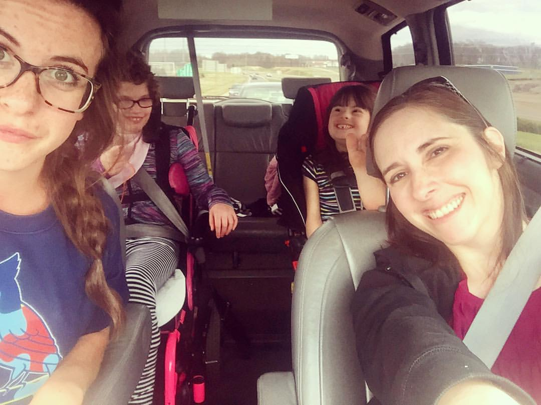 Erin riding in a car with their respite provider, and her two daughters in the back seats.