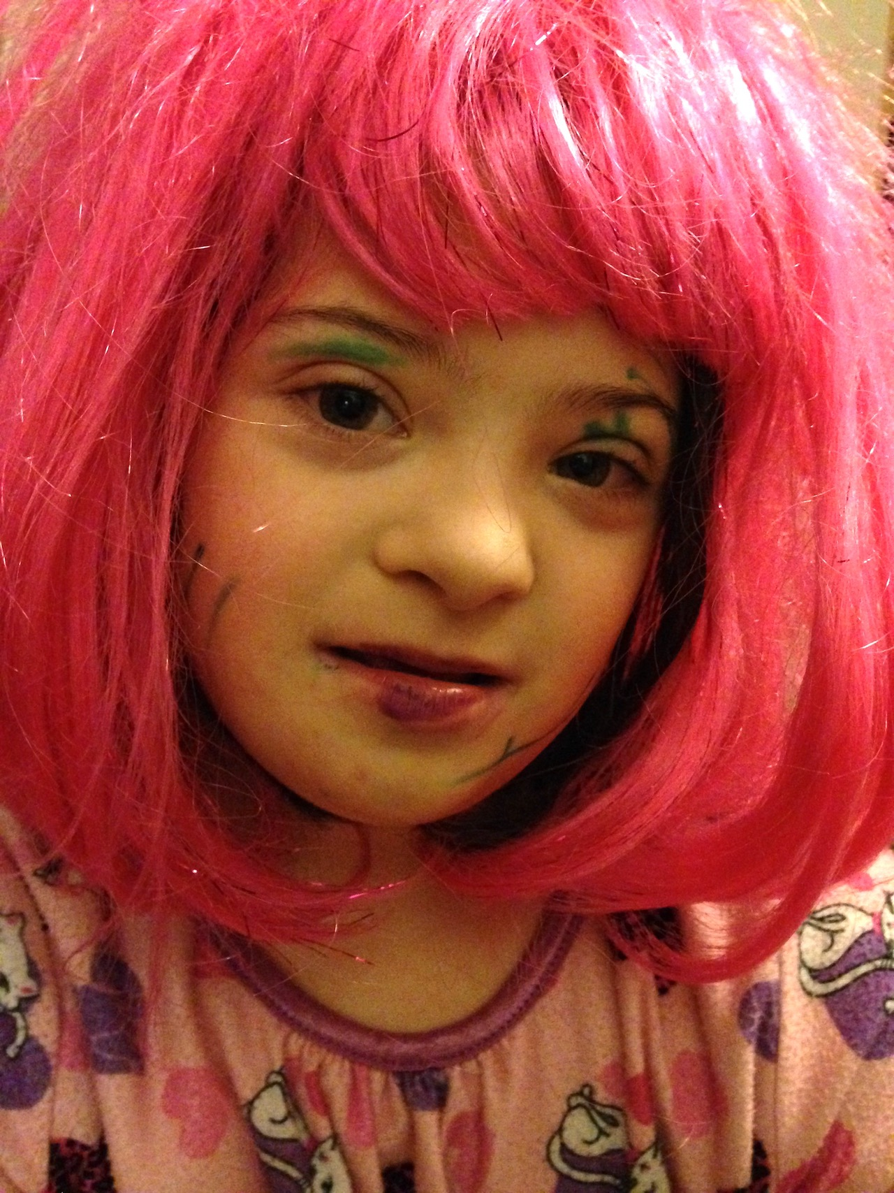 Little girl with pink wig and markers on her face for eyeshadow and lipstick