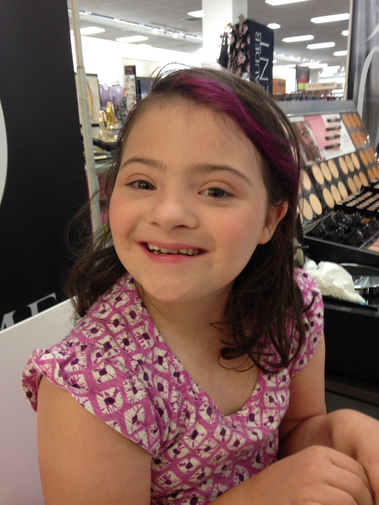 Little girl with Down syndrome wearing makeup and smiling