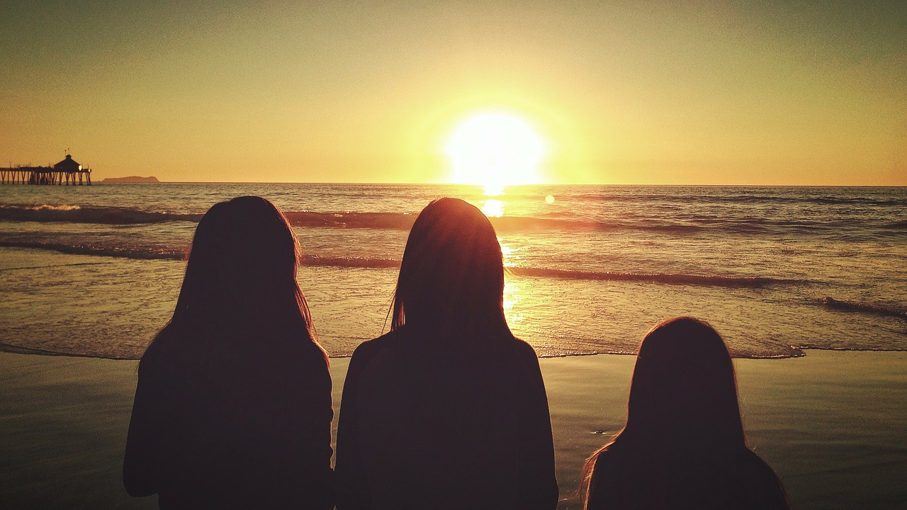 Three girls looking into a sunset. They look like shadows because of the setting sun. They are standing on the ocean shore.