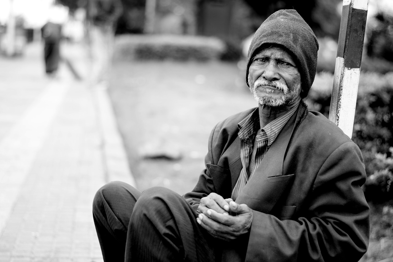 Black and white image of homeless man. He is looking at the camera, wearing a beanie on his head, mismatched clothes, hands together sitting on the floor