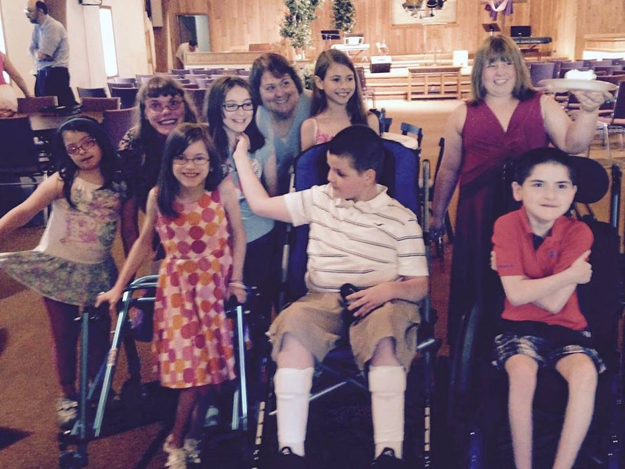 Image of several children with disabilities at church smiling at the camera
