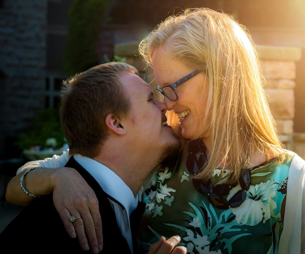 Mother face-to-face smiling at her son with Down syndrome
