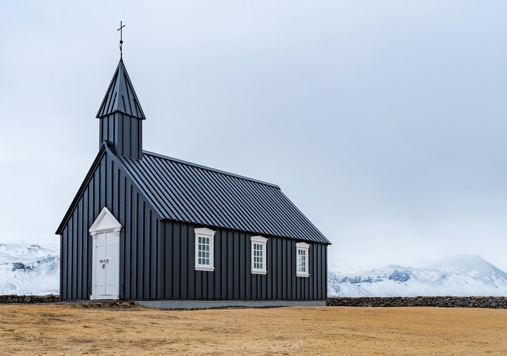 Image: dark gray barn-like church with white door and white windows sitting on empty field and snowy mountains in the background.