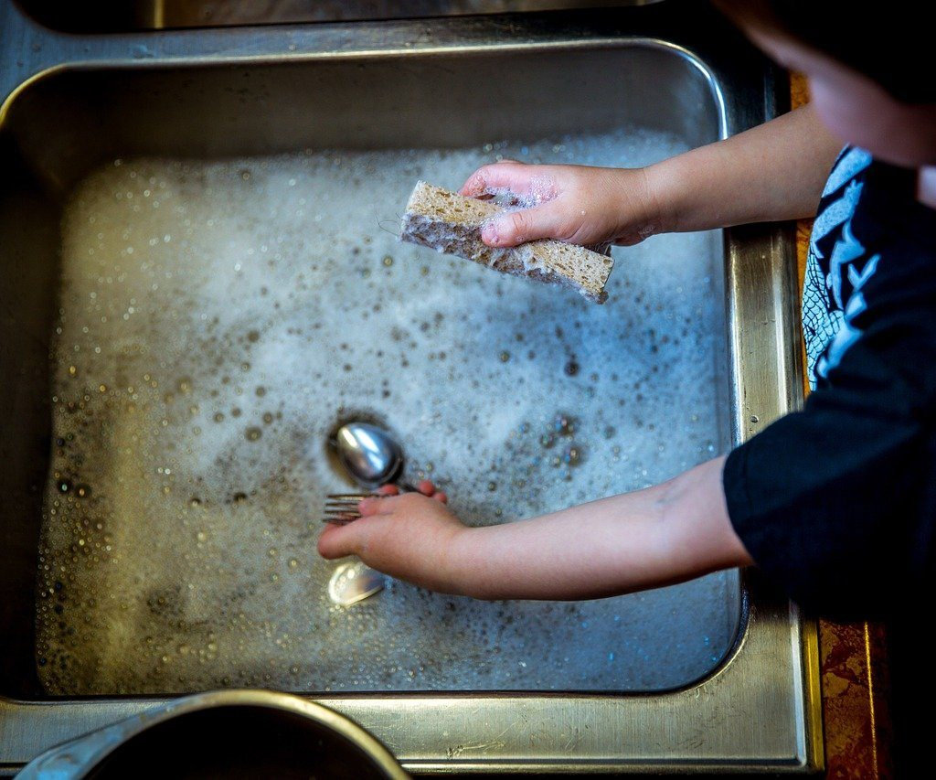 Image: soapy sink, you can see a spoon and the hand of a child holding a fork with one hand and a sponge with the other.