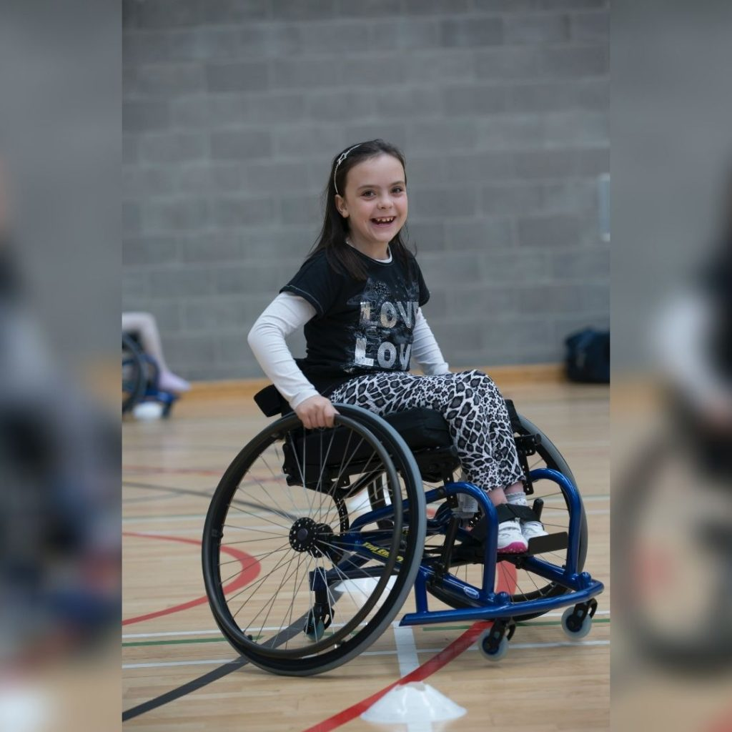 Girl in blue sports wheelchair smiling at camera. She is in a gymnasium and there is a blurry image of another wheelchair in the background.
